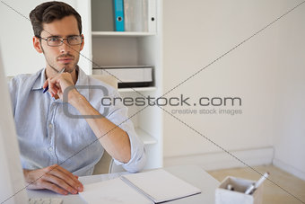 Casual businessman thinking at his desk