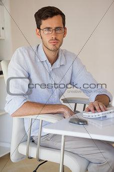 Casual businessman frowning at camera at his desk