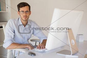 Casual businessman frowning at camera at his desk