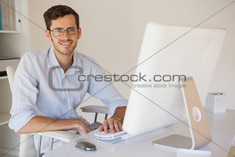 Casual businessman smiling at camera at his desk
