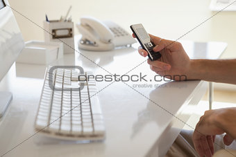 Casual businessman sending a text at his desk