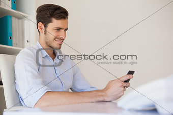 Casual happy businessman sending a text at his desk