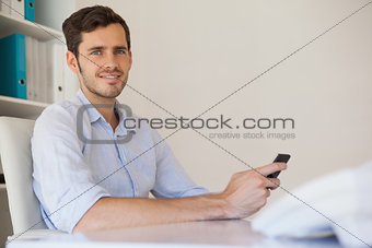 Casual happy businessman sending a text at his desk