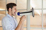 Casual businessman shouting through megaphone