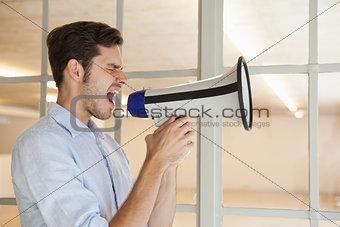 Casual businessman shouting through megaphone