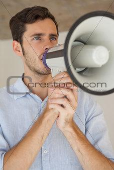 Casual businessman talking through megaphone