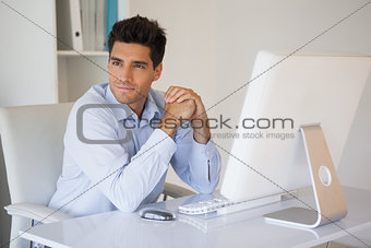 Casual businessman smiling at his desk