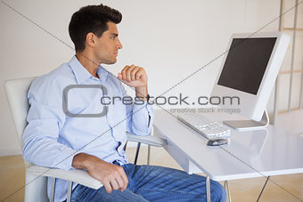 Casual businessman looking at computer screen