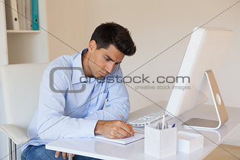 Casual businessman writing at his desk