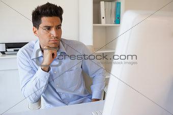 Casual businessman focusing at his desk