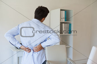 Casual businessman touching his sore back
