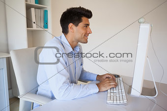 Casual businessman typing at his desk