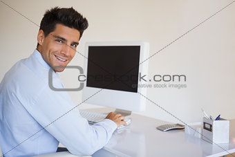 Casual businessman working at his desk smiling at camera
