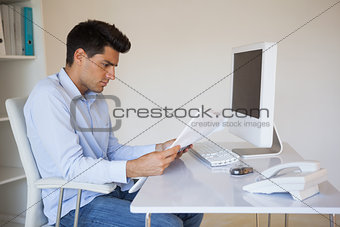 Casual businessman reading document at his desk