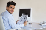 Casual businessman reading newspaper at his desk