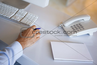 Casual businessman at desk with notepad and telephone