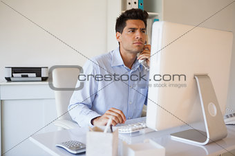 Casual businessman on the telephone at desk