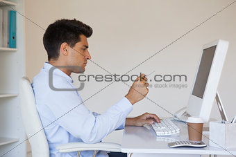 Casual businessman concentrating at his desk