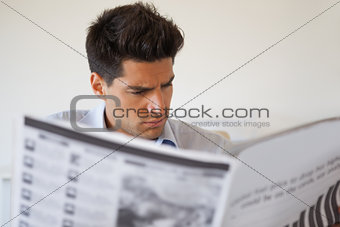 Casual businessman reading the newspaper