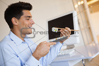 Casual businessman enjoying sushi at his desk