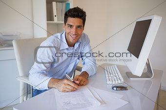 Casual businessman sitting at desk writing