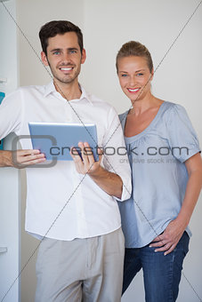 Casual business team smiling at camera man holding tablet