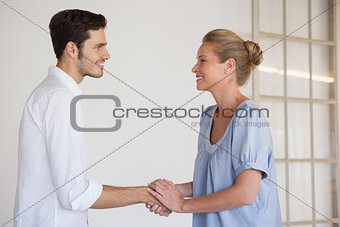Casual business woman shaking hands with man