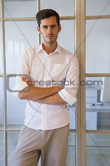 Casual businessman standing with arms crossed