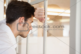 Casual worried businessman leaning against the window