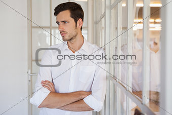 Casual upset businessman leaning against window
