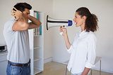 Casual businesswoman shouting at colleague through megaphone