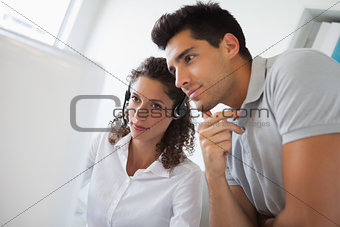 Casual businessman looking at colleagues computer
