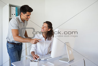 Casual business team smiling at each other at desk