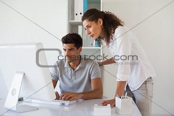 Casual business team looking at computer together at desk