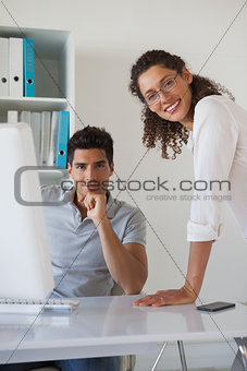 Casual business team smiling at camera together at desk