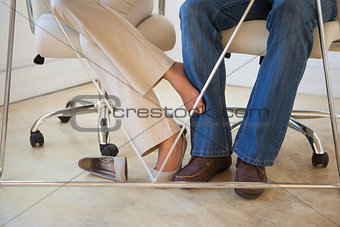 Casual businesswoman playing footsie with colleague under desk