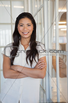 Casual businesswoman smiling at camera with arms crossed