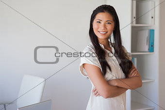 Casual businesswoman looking at camera with arms crossed