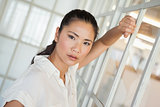 Casual frowning businesswoman leaning on window