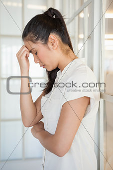 Casual upset businesswoman with head bowed