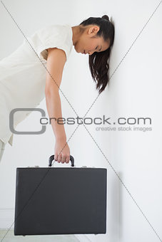 Casual businesswoman leaning against wall with briefcase