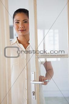 Casual businesswoman opening glass door