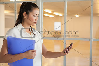 Casual businesswoman texting on phone holding folder