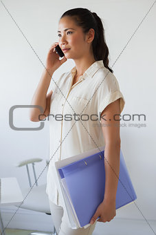 Casual businesswoman on the phone holding folder