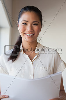 Casual businesswoman holding document and smiling at camera