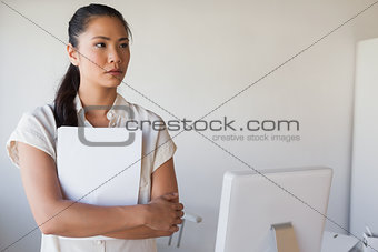 Casual businesswoman holding document while thinking