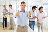 Casual boss giving thumbs up at camera in front of business team