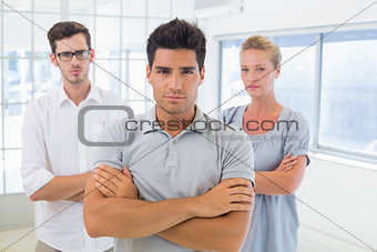 Casual business team looking at camera with arms crossed