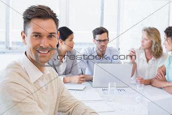 Casual businessman smiling at camera during meeting