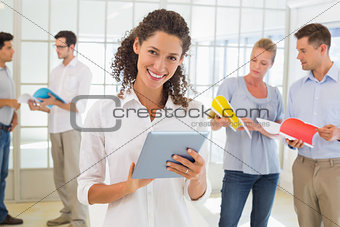 Casual businesswoman using tablet with team behind her
